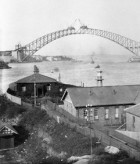 Harbour Bridge span nearly completed, with early buildings on Goat Island in the foreground, ca. 1932, image by Ted Hood, image courtesy SLNSW